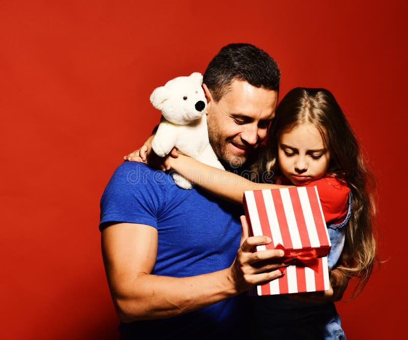 父亲节 拥抱爸爸的愉快的家庭女儿 免版税库存图片