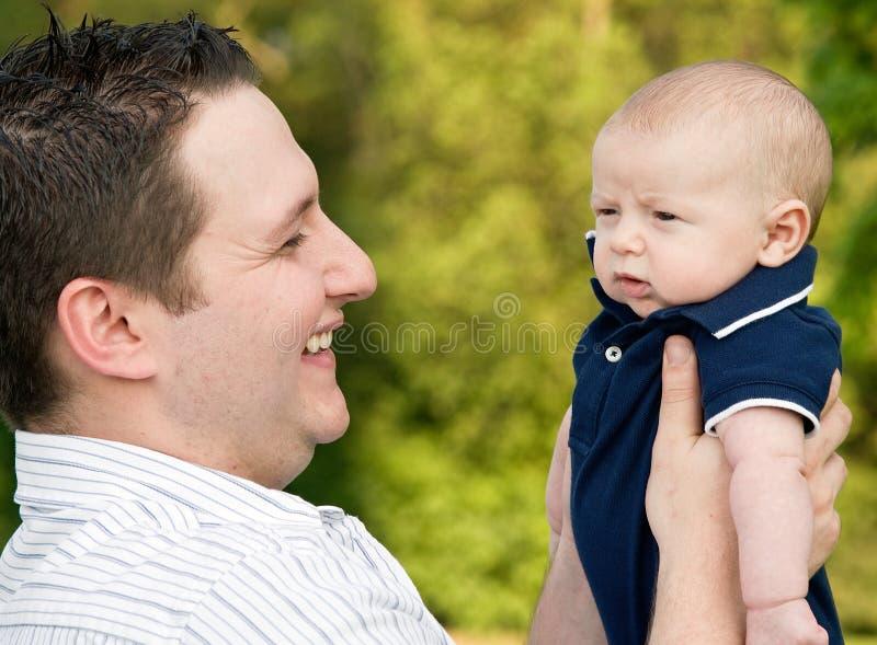 父亲藏品笑的儿子 免版税库存图片