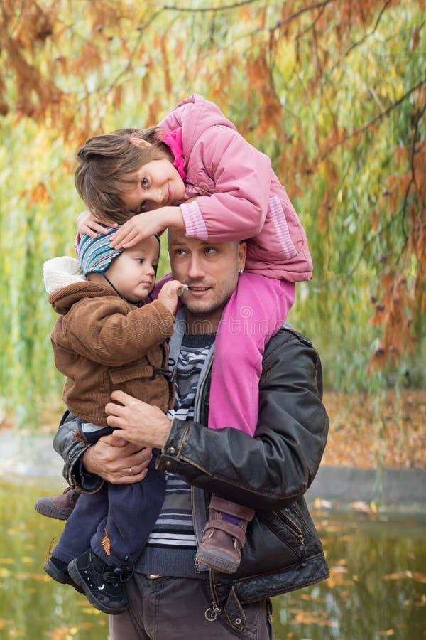 父亲运载的儿子和女儿肩扛 免版税库存图片