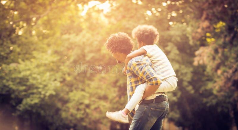 父亲运载的女儿扛在肩上 库存照片