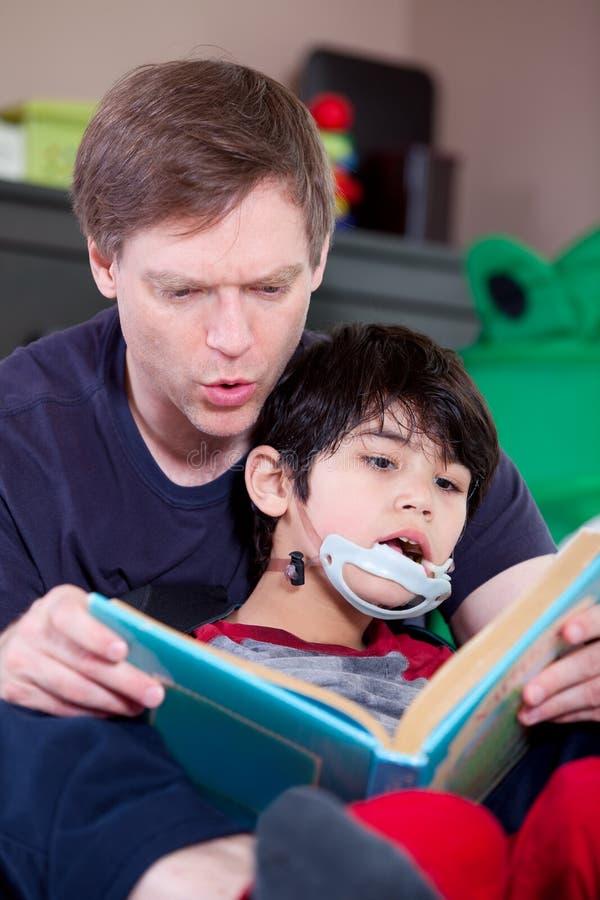 父亲阅读书使小儿子失去能力 免版税库存照片