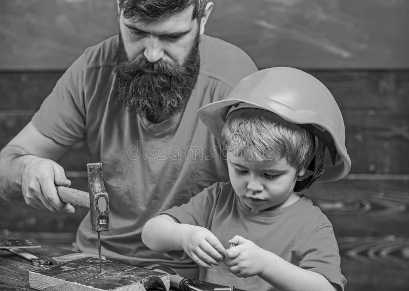 父亲,有胡子的父母教一点儿子的使用短钉和锤子 男孩,孩子繁忙在防护盔甲学会 库存图片