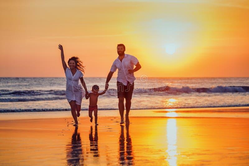 父亲,母亲,婴孩获得在日落海滩的一个乐趣 库存照片