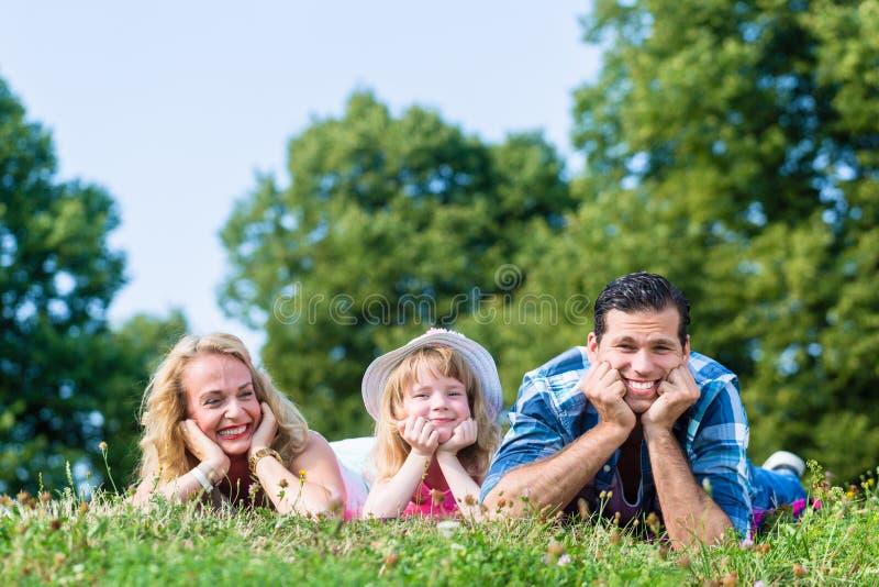 父亲,母亲,说谎在草的草甸的女儿 图库摄影