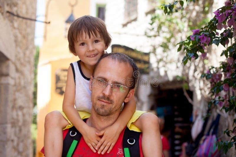 年轻父亲,运载他的他的脖子的小孩男孩,夏令时, 图库摄影