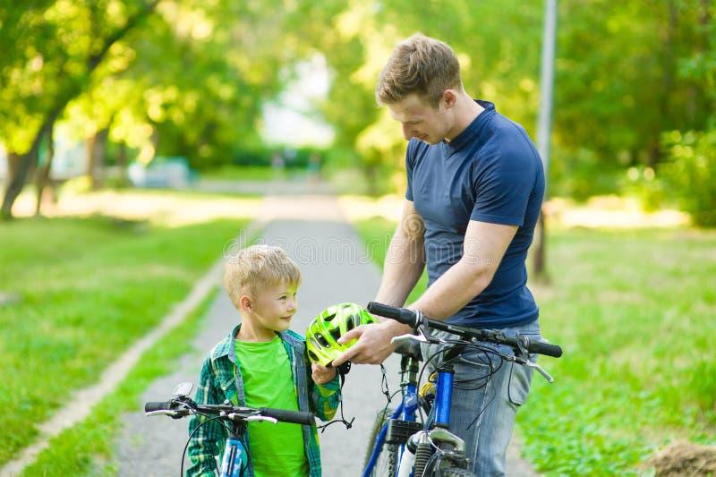 父亲给他的儿子一件自行车盔甲 免版税库存照片