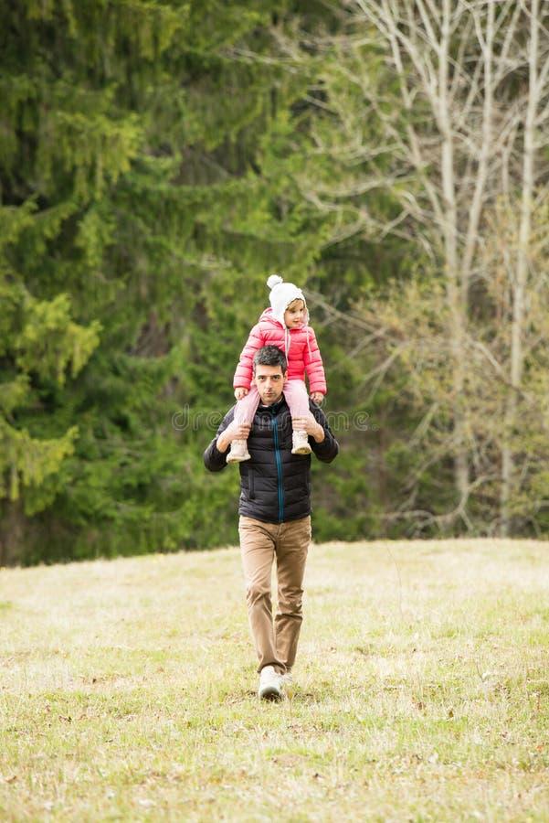 父亲给肩扛他的女儿 免版税库存图片