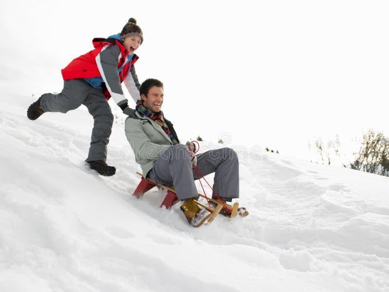 父亲sledding的儿子年轻人 免版税图库摄影
