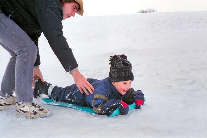 父亲sledding的雪儿子 图库摄影