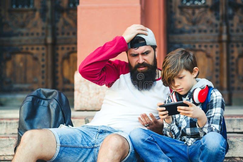 父子俩用智能手机 爸爸和儿子在户外共度时光 青少年玩电话游戏 父亲 免版税库存照片