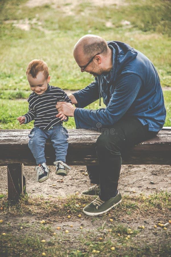父子坐在长凳上 免版税库存图片