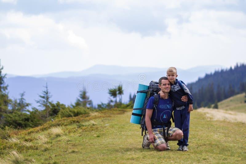 父子携背包一起在风景秀丽的夏日绿山远足 父子站在风景山 库存照片