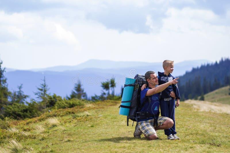 父子携背包一起在风景秀丽的夏日绿山远足 父子站在风景山 免版税库存照片