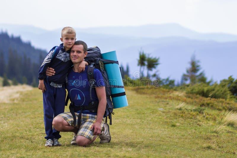 父子携背包一起在风景秀丽的夏日绿山远足 父子站在风景山 免版税库存图片