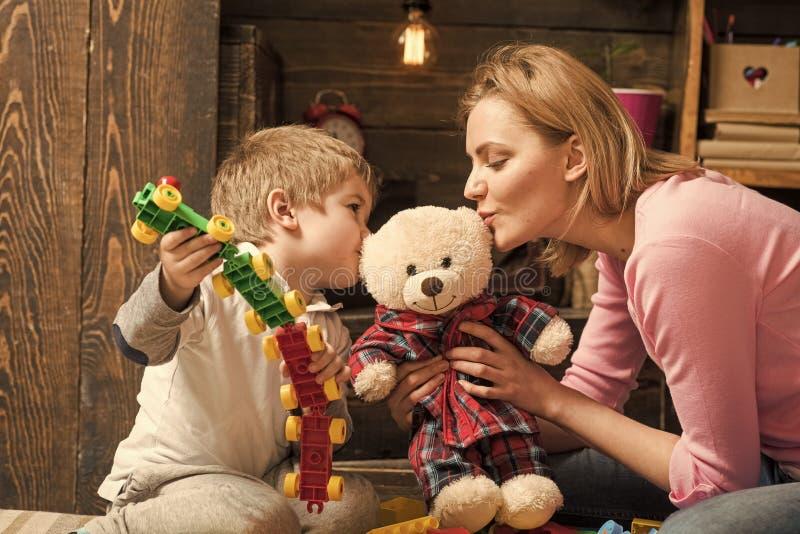 父母亲关注 仁慈和教育概念 母亲教儿子是亲切和友好的 托儿所木墙壁 免版税库存图片