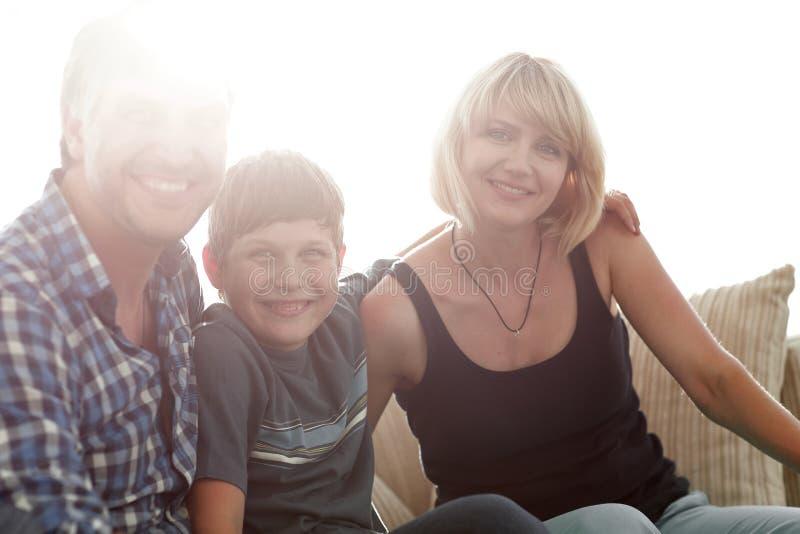 父母和他们的儿子在客厅和微笑坐挤作一团 库存图片