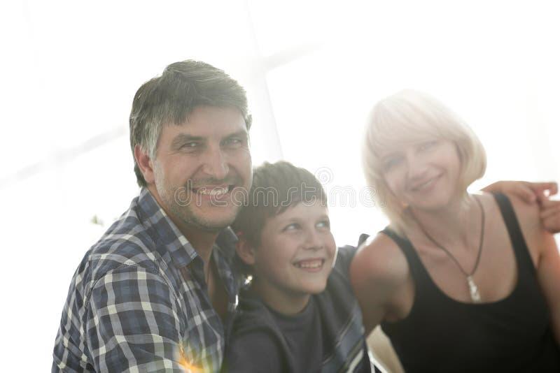 父母和他们的儿子在客厅和微笑坐挤作一团 库存照片