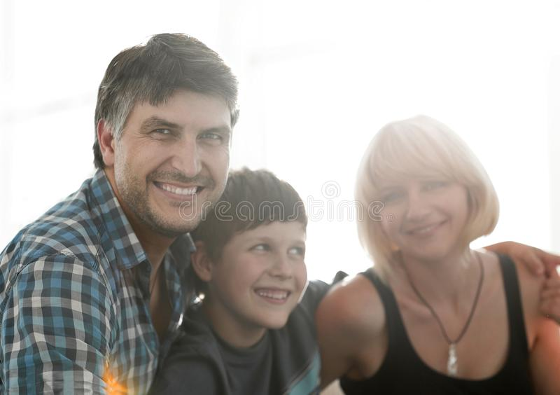 父母和他们的儿子在客厅和微笑坐挤作一团 图库摄影