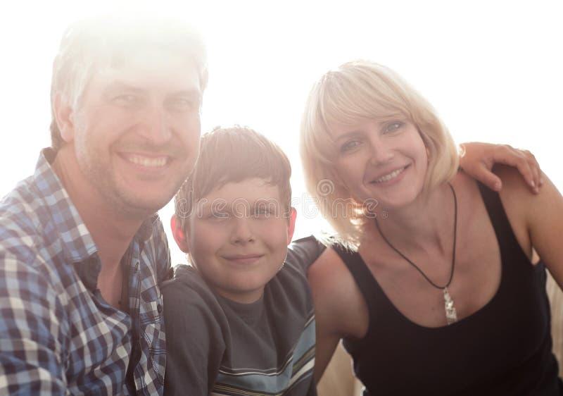 父母和他们的儿子在客厅和微笑坐挤作一团 免版税图库摄影