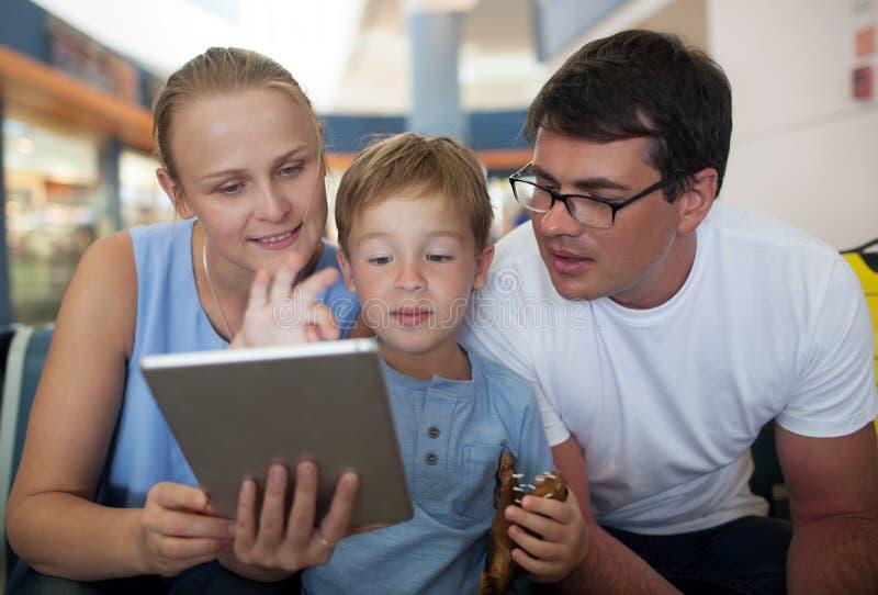 父母和儿子有片剂个人计算机的在机场 库存图片