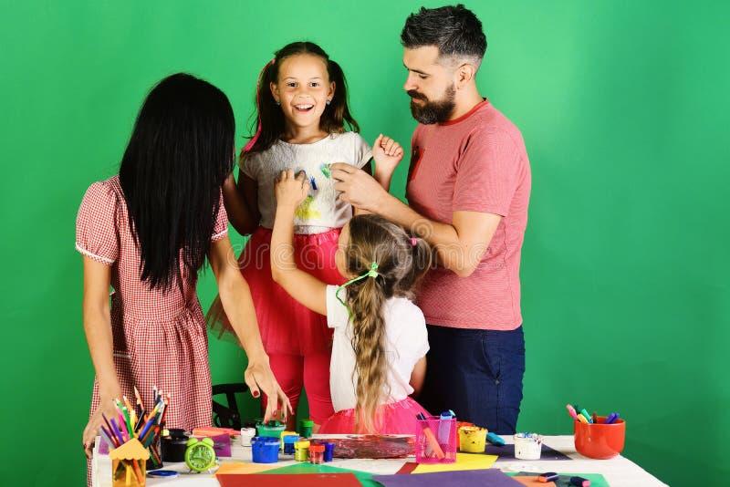 父母和儿童油漆与树胶水彩画颜料在女孩冠上 免版税库存照片
