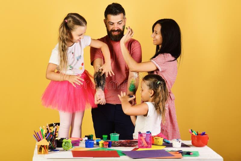 父母和儿童油漆在父亲用树胶水彩画颜料武装 免版税库存图片