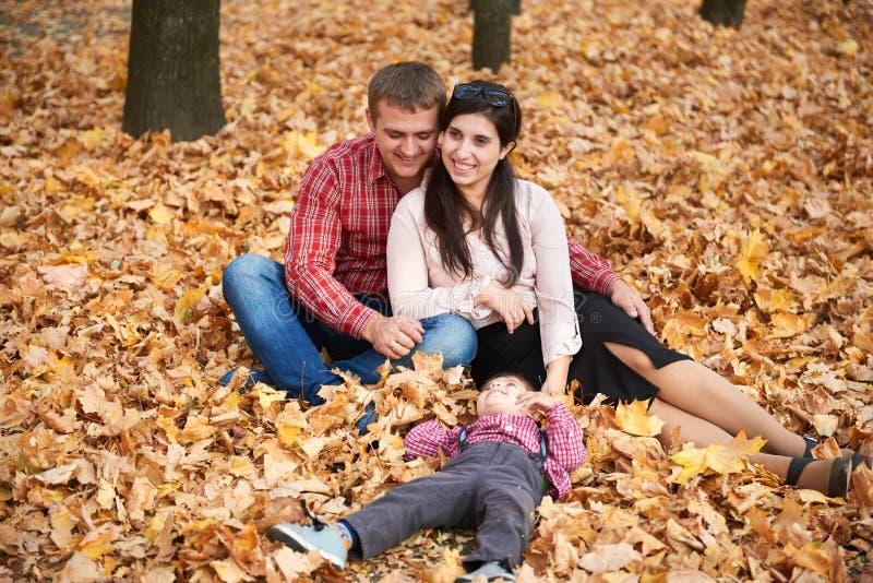 父母和儿童男孩在秋天城市公园坐 明亮的黄色树 免版税库存图片