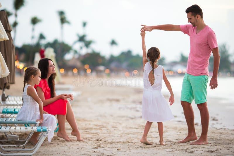 父母和可爱的两个孩子获得很多乐趣在他们的在海滩的暑假时 四口之家在爱,愉快 免版税库存照片
