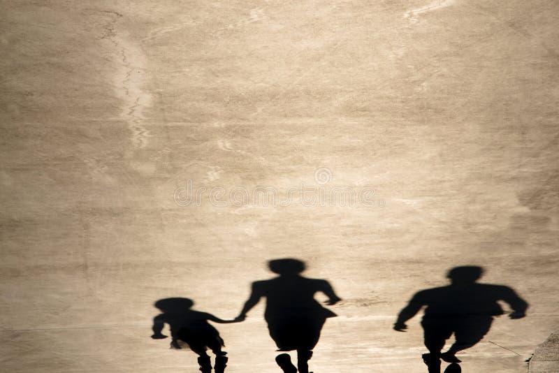 父母和女儿走的模糊的阴影 免版税库存照片