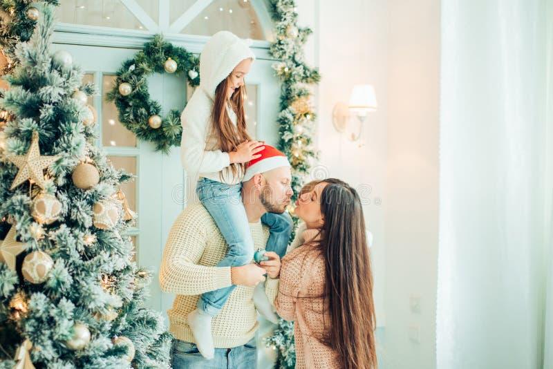 父母和婴孩获得乐趣在圣诞树附近 由圣诞树的爱恋的家庭 免版税图库摄影