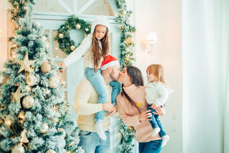 父母和婴孩获得乐趣在圣诞树附近 由圣诞树的爱恋的家庭 免版税库存图片