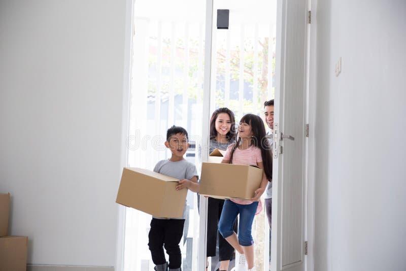 父母和孩子与纸板箱 安置移动新向 库存图片