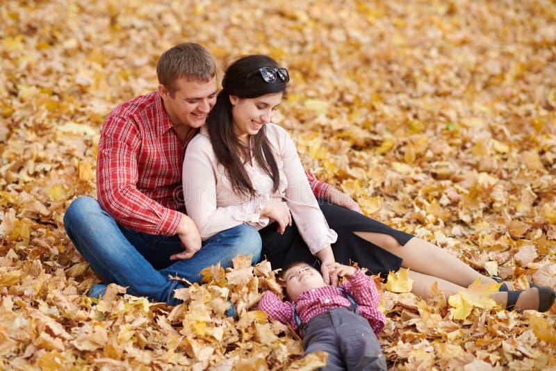 父母和孩子在秋天城市公园坐 明亮的黄色树 免版税库存照片