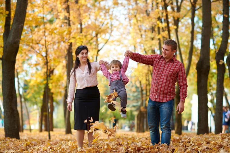父母和孩子在秋天城市公园走 明亮的黄色树 免版税库存照片