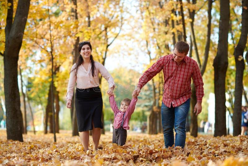 父母和孩子在秋天城市公园走 明亮的黄色树 免版税库存图片