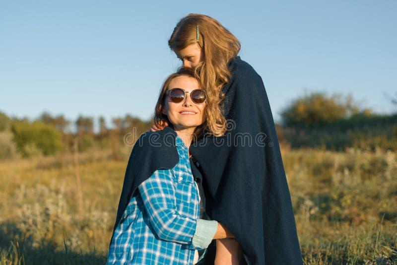 父母和孩子画象  愉快的一起拥抱母亲和小的女儿 自然背景,农村风景,绿色草甸 免版税库存图片