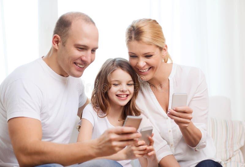 父母和小女孩有智能手机的在家 库存照片