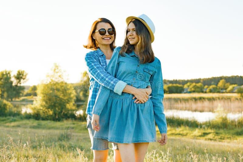 父母和少年、母亲和十四岁的女儿接受微笑本质上 背景日落,土气风景,绿色草甸 免版税库存照片
