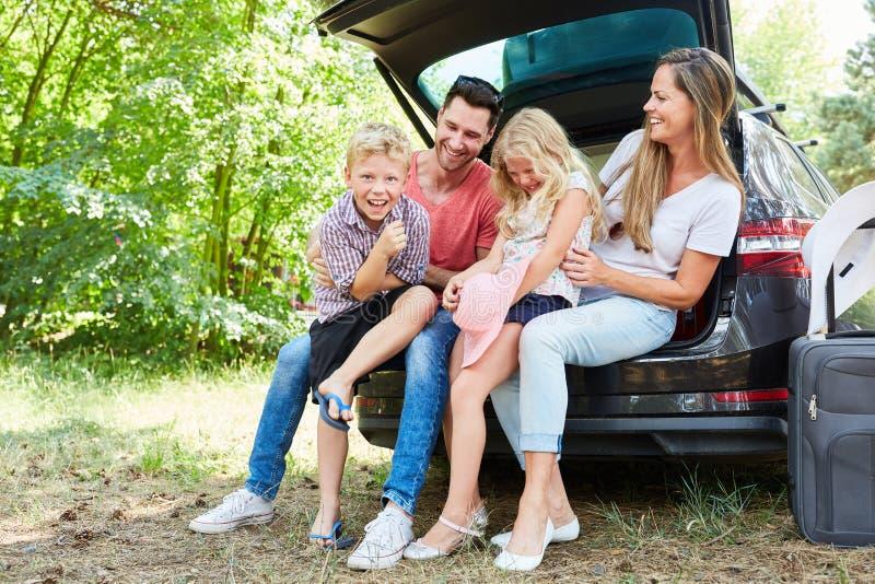 父母和笑的孩子在汽车 免版税库存照片