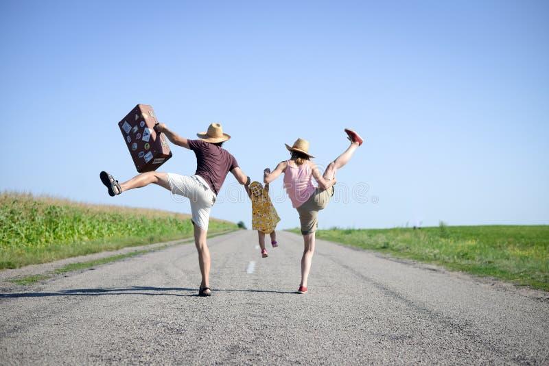 父母和婴孩带着跳舞的手提箱跳跃和 库存图片