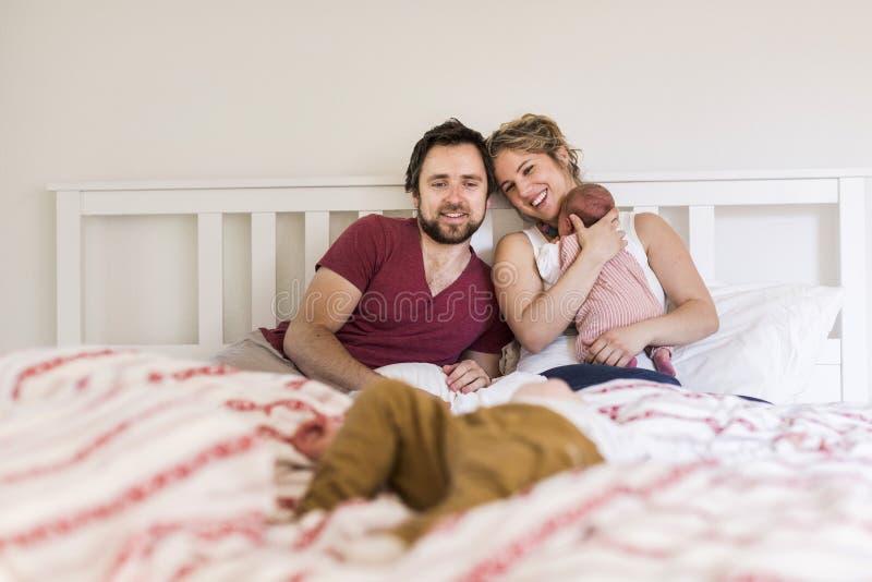 年轻父母在与他们逗人喜爱的小孩的床上 免版税库存图片
