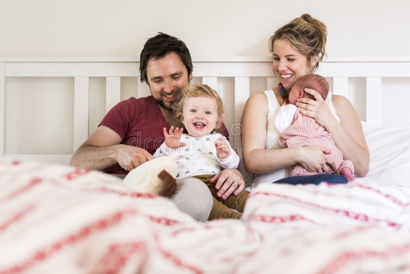 年轻父母在与他们逗人喜爱的小孩的床上 库存图片