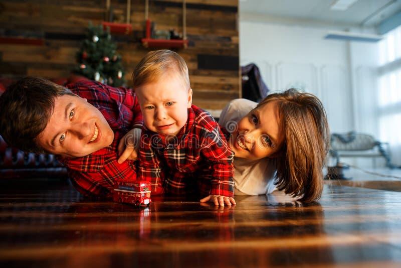 父母在地板上说谎 孩子在他们旁边爬行 他们直向前看 免版税库存照片