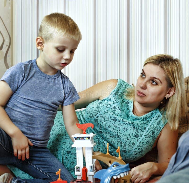 父母在家使用与他们的长沙发的小儿子 免版税库存图片