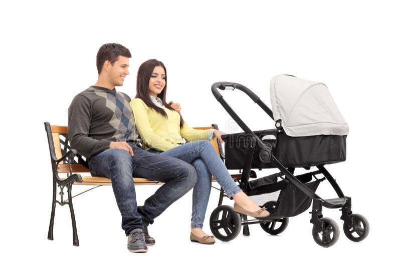 年轻父母坐与他们的婴孩的一条长凳 免版税库存图片