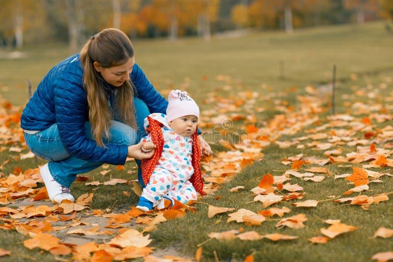父母培养跌倒做第一步的他的女儿 学会的女婴在秋天公园走 图库摄影