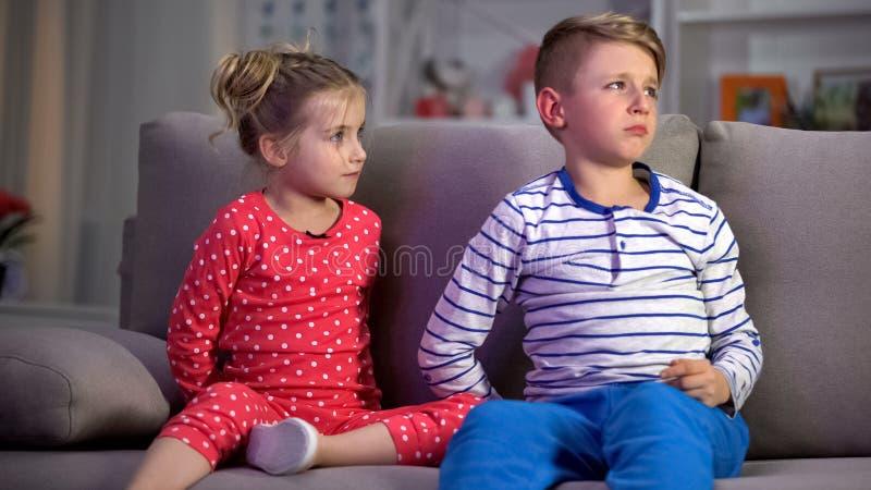 父母捉住的孩子,看着电视在晚上而不是睡觉,休闲 免版税库存图片