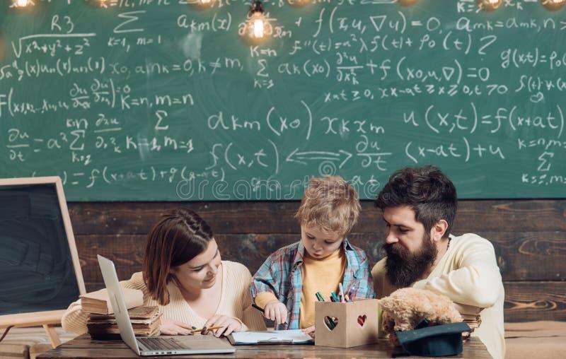 父母教儿子,在背景的黑板 关于他们的儿子的教育的家庭关心 Homeschooling概念 父项 库存照片