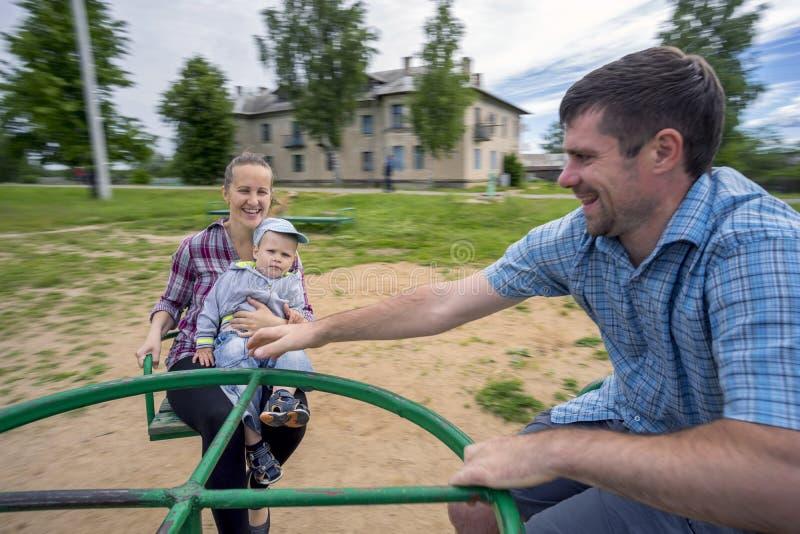 年轻父母有儿子的1 乘坐在转盘的3年 免版税图库摄影