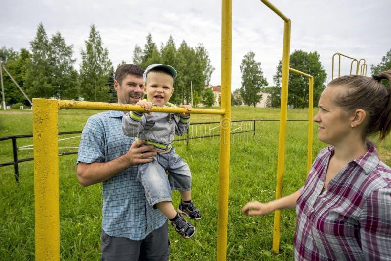 年轻父母有她的儿子的1 在老体育场的3年在村庄 库存图片